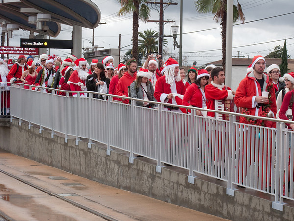 Santas getting off the train station in an orderly fashion. Santa would have been proud.