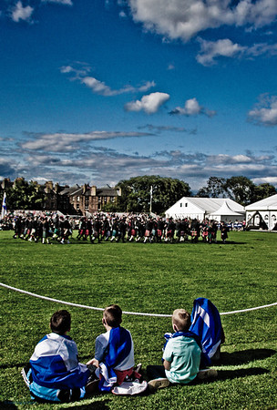 Pipeband watched by boys wrapped in saltire flags