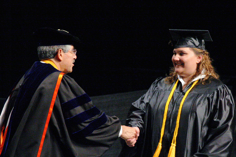 Hilliary shaking the hand of the Chancellor of TCC, as she walks across the stage... just look at that SMILE!