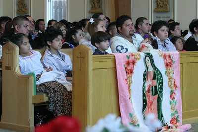 The Garcia Family, front row, draped an image of Our Lady of Guadalupe over the rail in front of their pew during the Mass at Church of the Good Shepherd, Cumming.