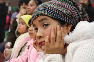 Claudia Cid, nine-years-old, watches the Good Shepherd Latino Dancers perform during the post Mass celebration in the gymnasium.