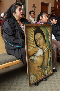 Beatriz, left, and Luz Ramirez sit with an image of Our Lady of Guadalupe and Pope John Paul II during the Dec. 12 Mass at Church of the Good Shepherd, Cumming.