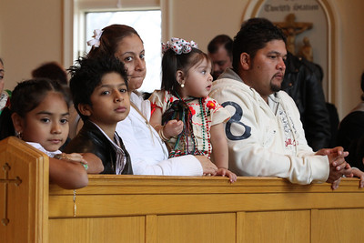 (L-r) Marbeil Garcia, her cousin Paublo, her aunt Maria, her cousin Lupita and her uncle Juan attend the Mass at Church of the Good Shepherd, Cumming, marking the feast of Our Lady of Guadalupe.