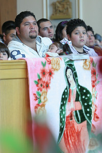 Juan Garcia holds his one-year-old daughter Lupita during the Our Lady of Guadalupe Mass as his sons Joandy, 4, left, and Christopher, 11, look on.
