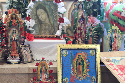 Religious articles depicting Our Lady of Guadalupe in many varieties were placed at the foot of the altar before the Mass honoring the blessed virgin.