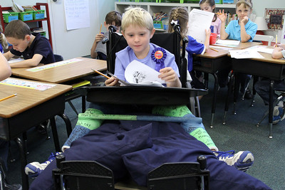 Wheelchair-bound Eli Clarkson wears a celebratory ribbon as he works on an exercise in his first grade class. His Atlanta school was named a 2011 National Blue Ribbon School of Excellence Sept. 15.    (Page 3, September 29, issue)