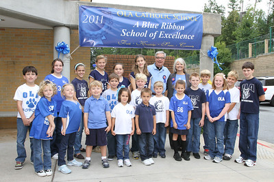 Dressed in blue clothing and spirit attire, Our Lady of the Assumption School students representing every homeroom, kindergarten through eighth grade, celebrate the Atlanta school's recognition as a 2011 National Blue Ribbon School of Excellence with parish pastor Marist Father James Duffy, back row, fifth from the right, and school principal Ann Nagel, back row, fourth from the right, Sept. 16.  (Page 1, September 29, issue)