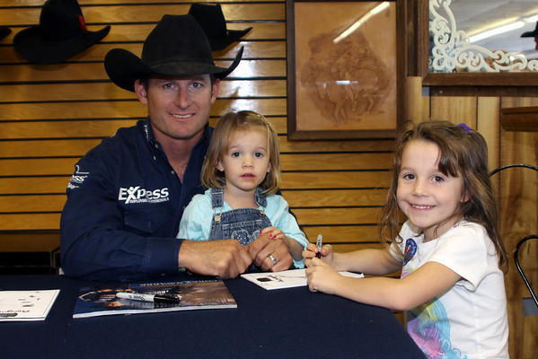 PRCA Circuit Finals Rodeo contestant Corey Navarre spends time with his children, Layna, 2, and Shyla, 6, during an autograph reception at  Crutcher's Western Wear in Duncan, Okla., Wednesday, Oct. 17, 2012.