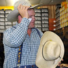 PRCA clown Justin Rumford tries on a new hat at Crutcher's Western Wear in Duncan, during an autograph reception to kick off the PRCA Prairie Circuit Finals Rodeo.