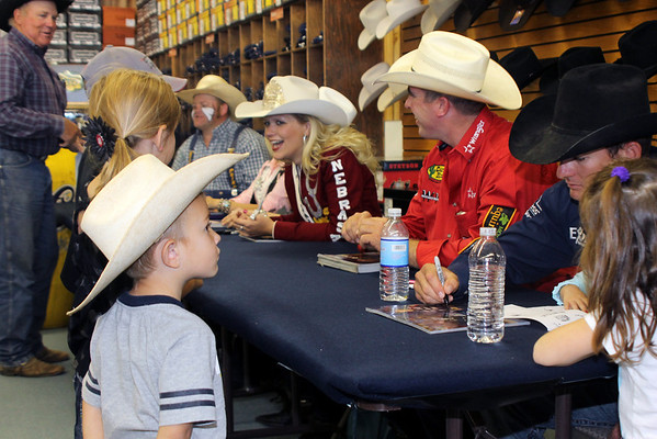 Four-year-old Cooper Dobbins, of Comanche, watches Corey Navarre autograph a photo for him at Crutcher's Western Wear in Duncan, Wednesday, Oct. 17, 2012.