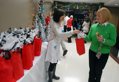 Hinsdale Central PTO member Connie Jaeger gives holiday gifts to faculty members including Administrative Assistant Marilyn Veldman during the appreciation holiday party and breakfast Thursday Dec. 20, 2012. Erica Benson—ebenson@shawmedia.com