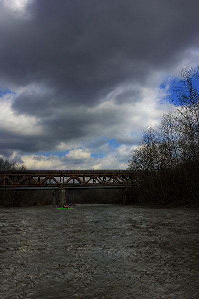 Bridge & Gloom<br /> An HDR photograph of the bridge and sky with someone kayaking in front of it.