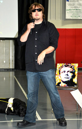 Debbie Blank | The Herald-Tribune<br /> With Echo snoozing at his feet, John Bramblitt shows students the most recent painting he completed of Hoosier James Dean, a movie actor who was born in Marion and died in a car crash at 24 in 1955.