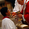 An altar server kneels while receiving Communion from Pope Benedict XVI during Mass marking the feast of Sts. Peter and Paul in Saint Peter's Basilica at the Vatican June 29. (CNS photo/Tony Gentile, Reuters) (June 30, 2008) See POPE-PALLIUM June 30, 2008.