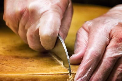Scoring the rind of the wheel to prepare it for cracking.