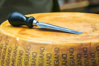 The wedge shaped knife that is pressed into the center of the wheel to help open the center of the cheese.