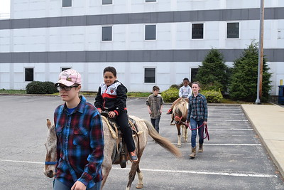 Sam Luptak Jr./NEWS Brothers Timothy, 6, front, and Alex, 5, ride the ponies provided by Squawk Creek Stables and the Mill Street Merchants.