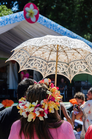Pacific woman wearing a garland of flowers and carrying a lacey sun umbrella Pasifika Western Springs