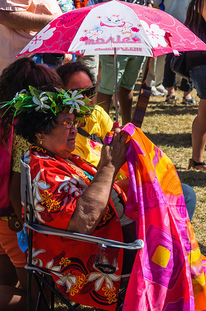 Pacific woman in bright coloured clothing watching stage presentation Pasifika Western Springs