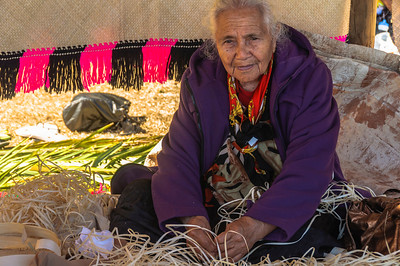 Elderly pacific woman weaving inside tent Pasifika Western Springs