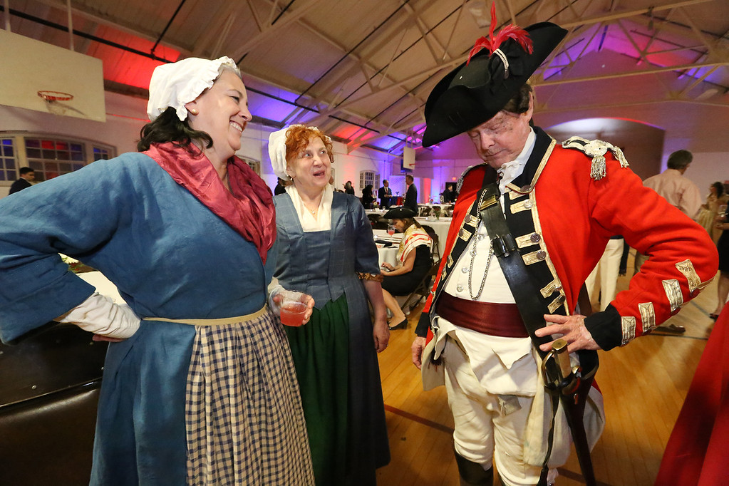 . Patriots\' Ball at Concord Armory. From left, K.C. Winslow of Concord, Kimberley Connors of West Concord, and Don Beale of Rosendale, NY, in the uniform of the British Light Dragoon. (SUN/Julia Malakie)