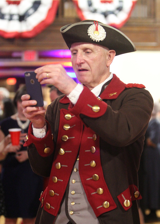 . Patriots\' Ball at Concord Armory. Roy Kring of Bedford, a member of the Bedford Minuteman Company, takes a photo. (SUN/Julia Malakie)
