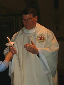 Father Paul lights a candle from his own candle's flame.