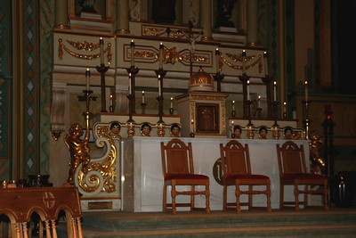 A view of the altar with dark haired cherubs. Mission Santa Clara. I'm sad to see the unfortunately common arrangement of chairs with their backs to the Tabernacle.