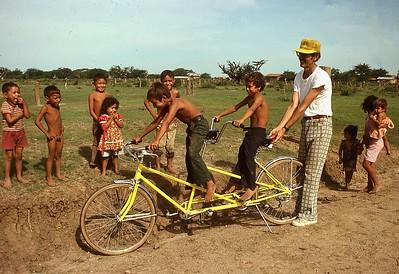 Gilbert Clift showing kids at El Provenir how to ride a tandum bike 1979