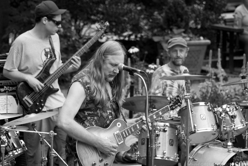 A guitarist, bassist and drummer performing in a concert at Pritchard Park in downtown Asheville