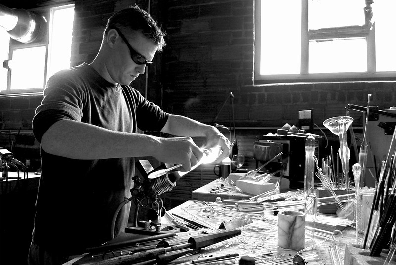 Alex Greenwood and Logan McSporran work with flame to make art out of glass at Asheville Glass Center in Phil Mechanic Studios in the River Arts District in Asheville, NC