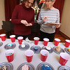 4th annual Cupcake Festival, to benefit Friends of the Lawrence Library in Pepperell. Jen Griffith, left, and Diane Temple, president of Friends of the Lawrence Library, both of Pepperell, count up the money in each cup to determine winners. People could vote for a quarter per vote. (SUN/Julia Malakie)