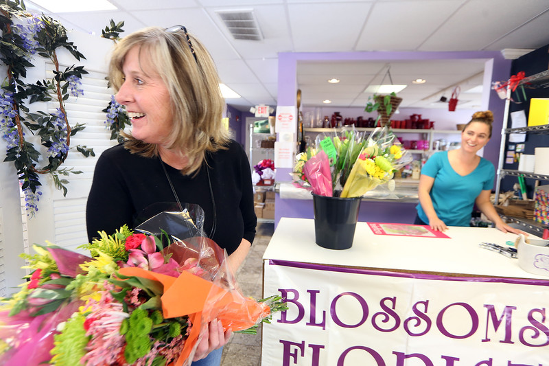 Blossoms Florist owner Darlene Cambra of Derry, N.H., left, and floral designer Mindy Hurst of Nashua, head out in search of recipients as they participate in the Society of American Florists' annual Petal It Forward event, giving two bouquets to random people, one to keep and one to give to someone else. They don't have much pedestrian traffic so they were going to local businesses. (SUN/Julia Malakie)
