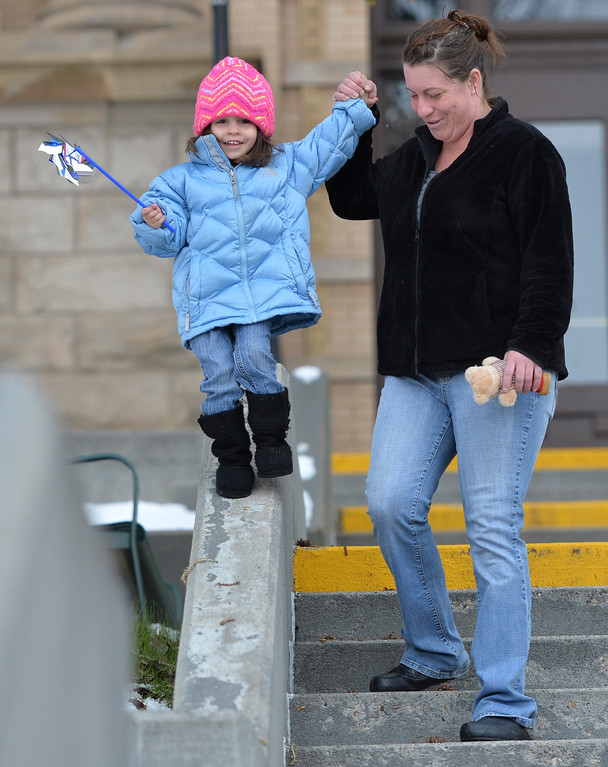 """Justin Sheely   The Sheridan Press<br /> Ann Ferber walks Eleanor Ferber, 3, along a wall during """"Pinwheels for Justice"""" pinwheel garden project Wednesday at the Sheridan County Courthouse. Sheridan County Public Health and Compass hosted the project to raise awareness and on child abuse and neglect. Funds raised from the pinwheel garden benefit education programs at Prevent Child Abuse Wyoming."""