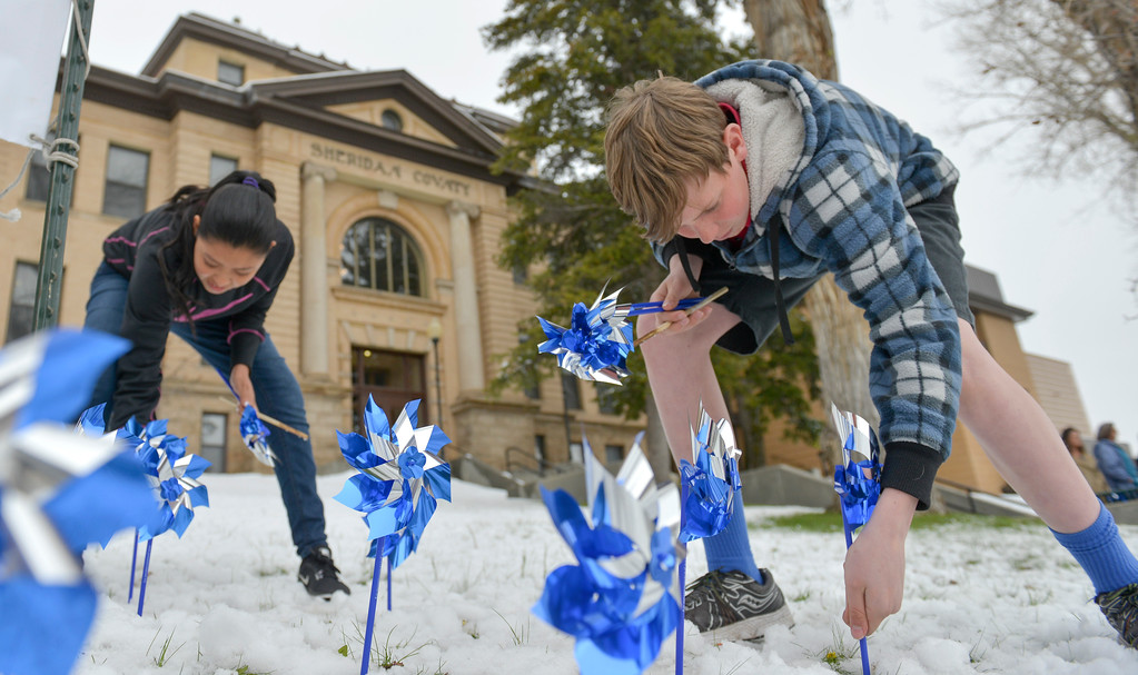 """Justin Sheely   The Sheridan Press<br /> Holy Name Catholic School middle schoolers Silvia Garza, left and Kevin Woodrow push pinwheels into the ground during """"Pinwheels for Justice"""" pinwheel garden project Wednesday at the Sheridan County Courthouse. Sheridan County Public Health and Compass hosted the project to raise awareness and on child abuse and neglect. Funds raised from the pinwheel garden benefit education programs at Prevent Child Abuse Wyoming."""
