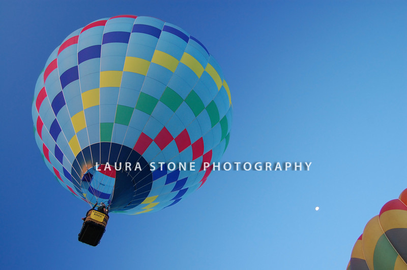 A hot-air balloon takes flight in the early morning at a balloon festival. Moon in the distant sky.