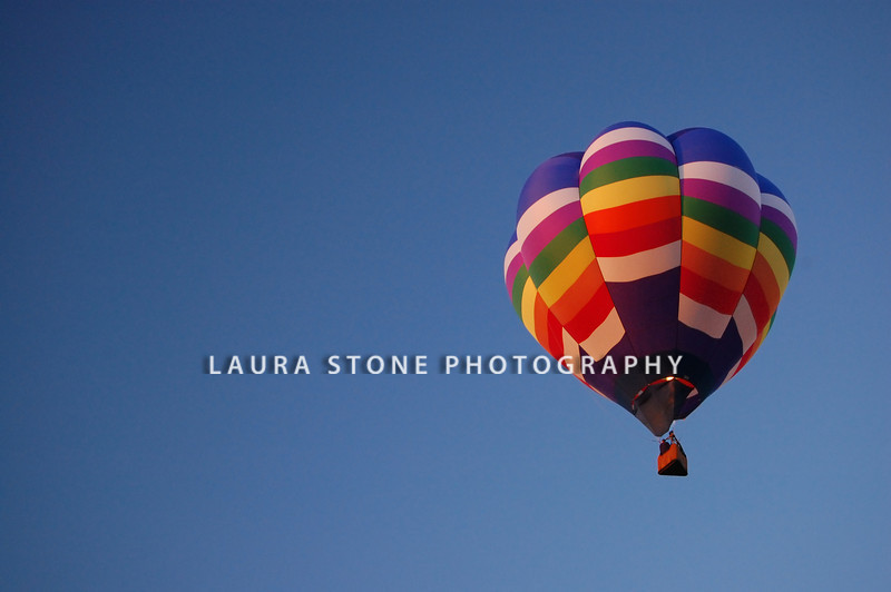 A multi-colored hot air balloon rises into a blue sky.