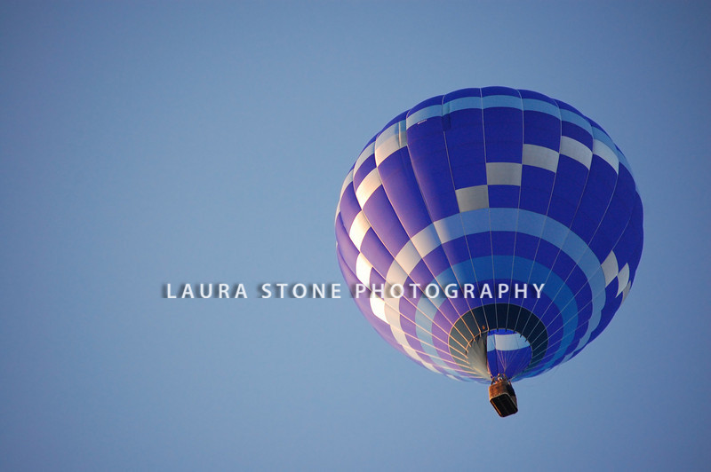 A blue hot air balloon rises into the sky on a bright summer morning.
