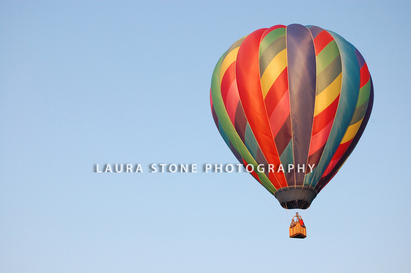 A rainbow colored hot-air balloon in the sky on a beautiful summer morning.