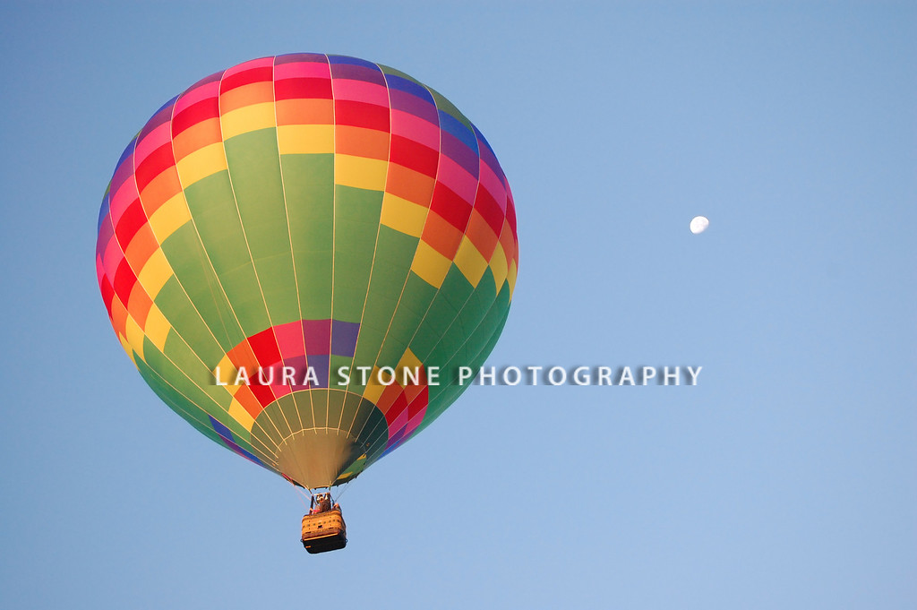 A rainbow colored hot-air balloon in the sky on a beautiful early summer morning. Moon in the distance.