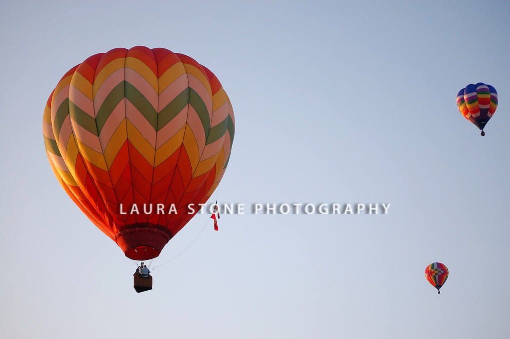Three hot-air balloons take flight at a balloon festival event