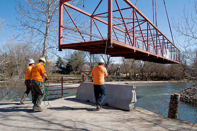 As the crane lowers the Plantation Bridge, crew workers carefully guide the bridge into place.