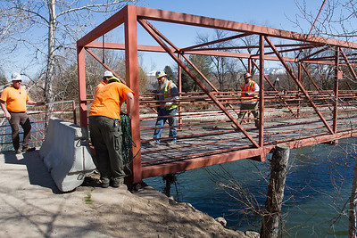 """With the bridge down, the crew takes the """"first walk"""" across the Boise River and inspects the footings to make sure all is well."""