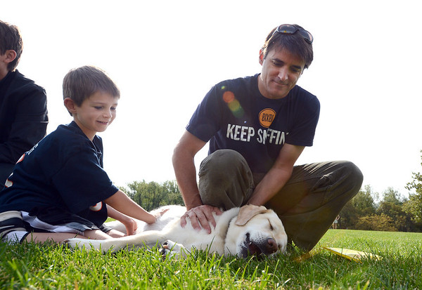 "TJ Rowan and his dad Todd, try to get their dog, Hera, to play dead for the Play-Dead-A-Palooza on Sunday at Scott Carpenter Park.<br />  Bixbi Pet (makers of 100 percent USA sourced dog treats) set the world record for 11 dogs playing dead at once. A world record effort, supported by RecordSetter, is to raise awareness about tainted dog treats.<br /> For more photos and a video of the dogs, got to  <a href=""http://www.dailycamera.com"">http://www.dailycamera.com</a>.<br /> Cliff Grassmick  / September 23, 2012"