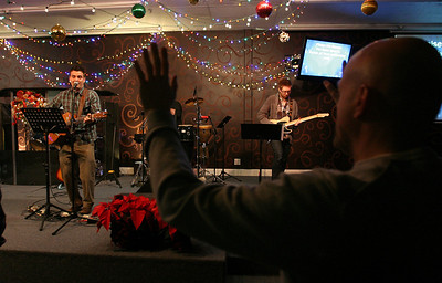 A church member raises his hands in praise as Worship Pastor Brandon Swanner, left, leads the congregation in song Sunday morning, December 11, 2011 at Pleasant Valley Community Church in Owensboro, KY. Guitatist Joe Hearne plays his part at right.