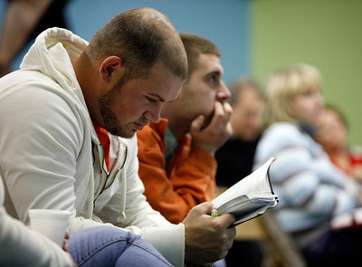 Brandon Griffith, left, reads his Bible while Beau Worth listens during the adult Sunday School class Sunday morning, December 11, 2011 at Pleasant Valley Community Church in Owensboro, KY.