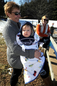 1/16/2010 Mike Orazzi | Staff A bundled up Ryan Zima waits for his uncle Joe Dolan of Bristol to take the polar plunge at Camp Sloper in Southington.  Dolan is a member of the Southington fire department and Ryan is being held by his grandmother Debbie, also of Bristol.