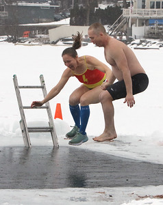Polar plunge to benefit Special Olympics, at the Shoreline Beach Club in Tyngsboro. Mindy Bolton and her partner Sam Talbot of North Andover leap together. Only members of the same household could do the plunge together, for social distancing. (SUN/Julia Malakie)