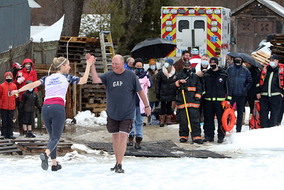 Beth Craig of Tyngsboro, one of the organizers, high fives James Enwright of Dracut, owner of the Shoreline Beach Club, who was going next, at the polar plunge to benefit Special Olympics, at the Shoreline Beach Club in Tyngsboro. (SUN/Julia Malakie)