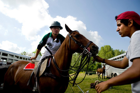 """Horse groomer Gabrielle Saccullo, from Argentina, holds the horse as rider Ignacio Saracco, of team Hospice Care Leadership, mounts before the start of a polo match at Ashlawn Farms north of Boulder, Saturday, June 19, 2010. <br /> <br /> For a video of the game, please visit  <a href=""""http://www.dailycamera.com"""">http://www.dailycamera.com</a><br /> Kasia Broussalian"""